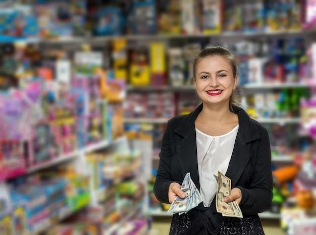 Donna che conta le banconote del dollaro nel negozio di giocattoli