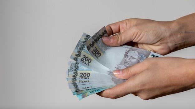 Donna che conta nuovi soldi brasiliani