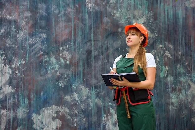 Donna in tuta e casco che tiene il blocco note e posa per la macchina fotografica su sfondo grigio