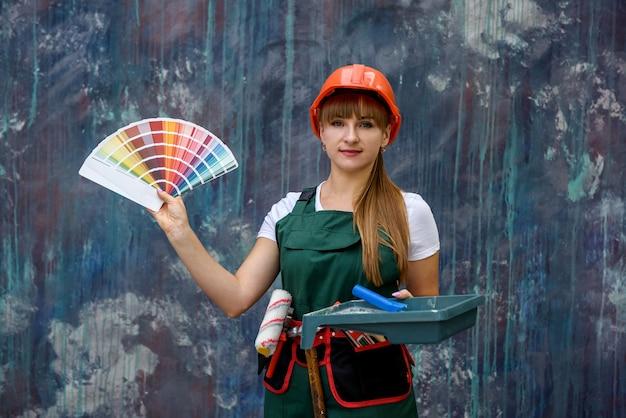 Donna in tuta in posa con campione di colore in ventola su sfondo colorato