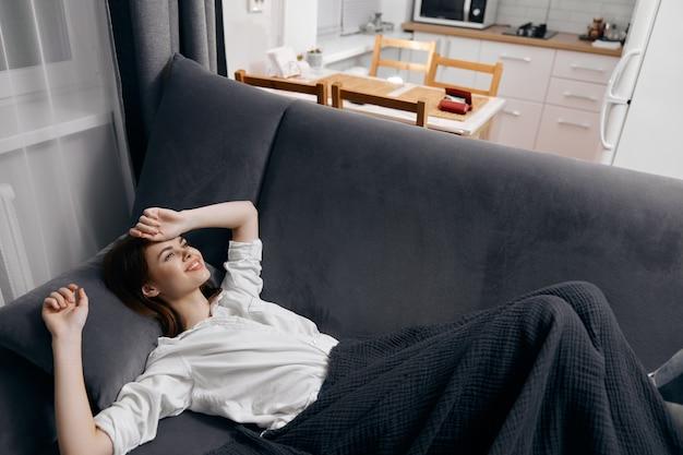 La donna coperta da una coperta è sdraiata sul divano e guarda la finestra sullo sfondo.