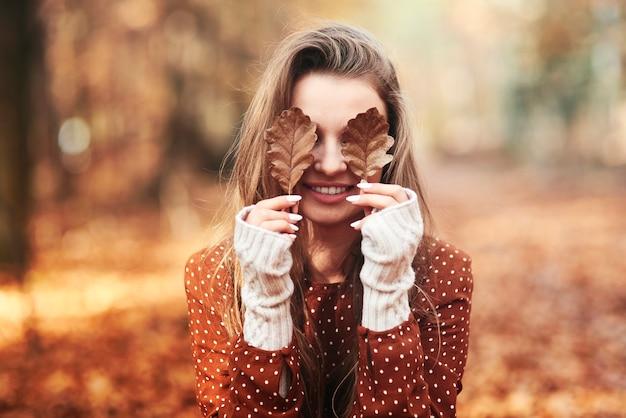 Donna che copre gli occhi con foglie autunnali