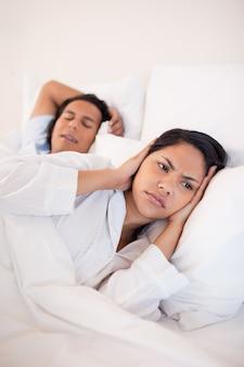 Donna che copre le orecchie per bloccare i suoi fidanzati russare