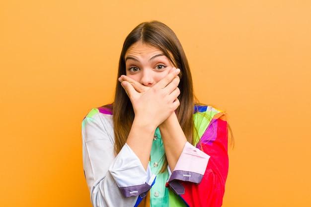 Donna che copre la bocca con le mani con un'espressione scioccata e sorpresa, mantenendo un segreto o dicendo oops