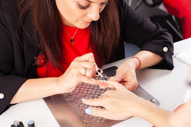 La donna copre le unghie dei clienti con un fissatore di vernice trasparente