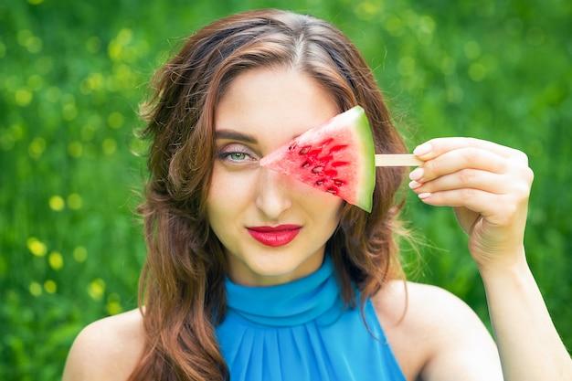 La donna copre l'occhio di anguria.