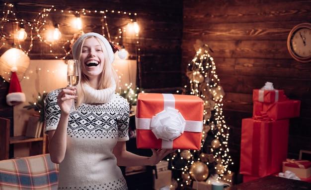 Il maglione lavorato a maglia accogliente della donna gode dell'atmosfera natalizia a casa. natale sta arrivando. decorazione interna domestica dell'albero di natale. il cappello di babbo natale dei vestiti invernali della ragazza celebra il natale e il felice anno nuovo.