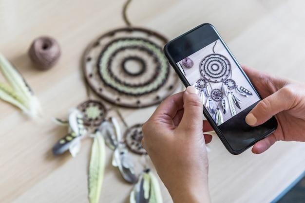 L'artigiano che fotografa l'acchiappasogni usa lo smartphone in officina per la pubblicità su internet