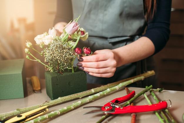 Donna che crea bouquet decorativo di fiori.