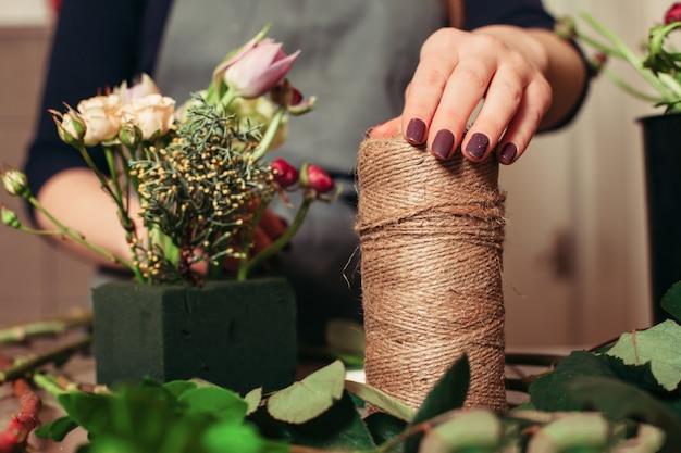 Donna che crea bouquet moderno di fiori diversi