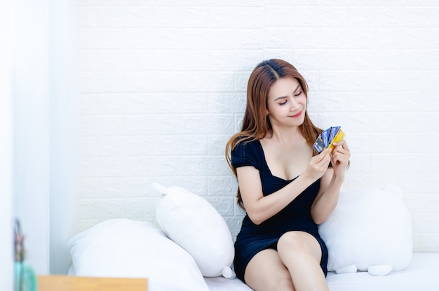 Le donne d'affari della carta di credito e della donna parlano al telefono e guardano l'idea di affari della carta di credito
