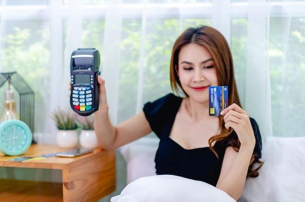 Donna e carta di credito con un dispositivo di scorrimento della carta di credito nel letto, il concetto di gestire un business online in ogni momento