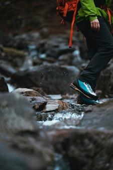 Donna che attraversa il torrente roccioso