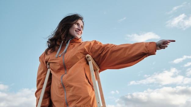 Una donna con le stampelle indica con la mano. riabilitazione dopo trauma arto