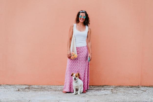 Donna cane carino donna che cammina per la città, con in mano un sacchetto di cotone con frutta.