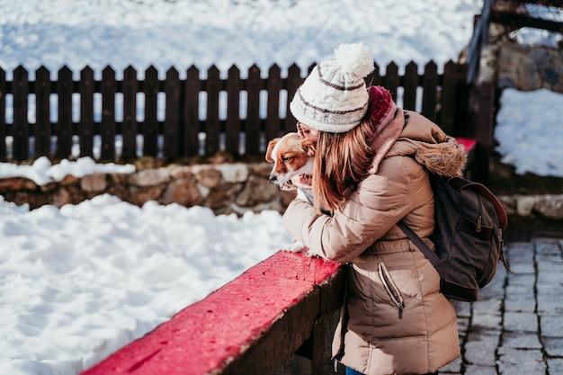 Donna e simpatico cane jack russell godendo all'aperto in montagna con la neve.