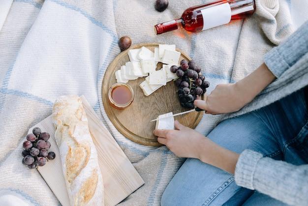 La donna taglia il formaggio su una vista dall'alto di picnic