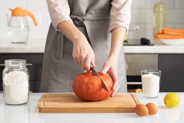 Una donna taglia una zucca per fare una torta nella sua cucina