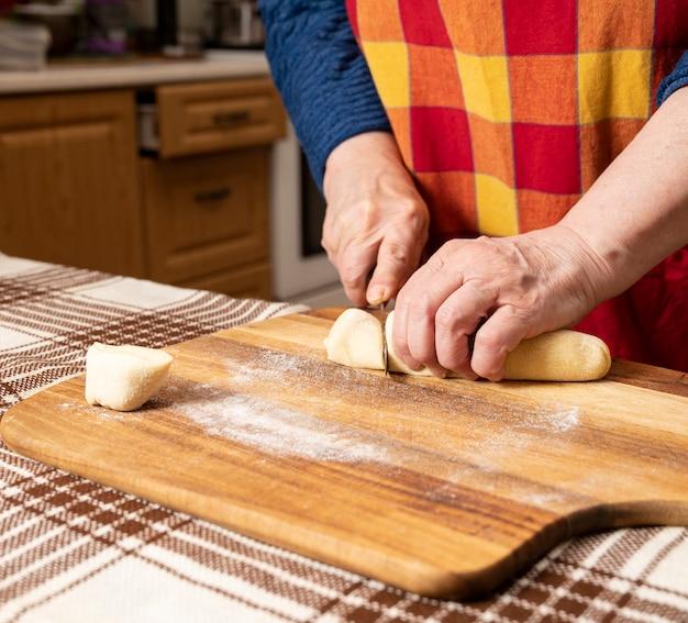 Donna che taglia la pasta con un coltello sul tavolo della cucina.