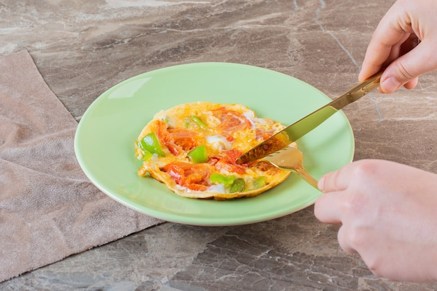 Donna che taglia pizza italiana con un coltello su pezzi di tessuto, sullo sfondo di marmo.