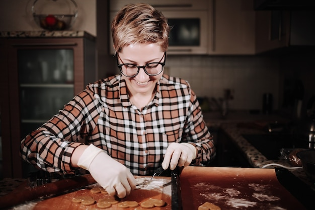 Donna che taglia un po 'di pasta di pan di zenzero con un cookie cutter in metallo