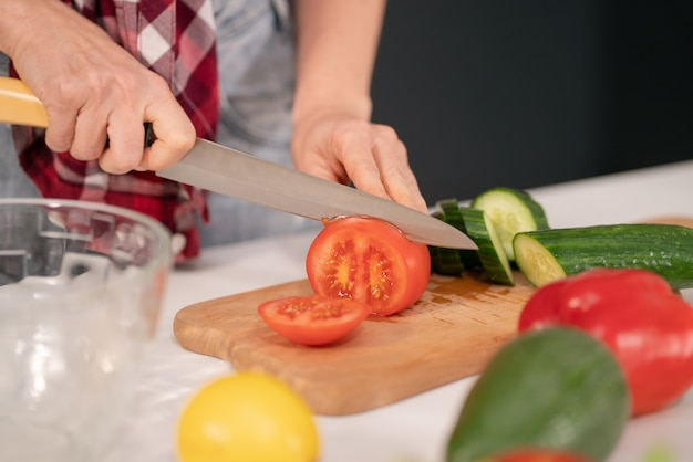 Donna che taglia pomodoro e cetriolo a bordo prepara insalata di verdure per una cena in famiglia