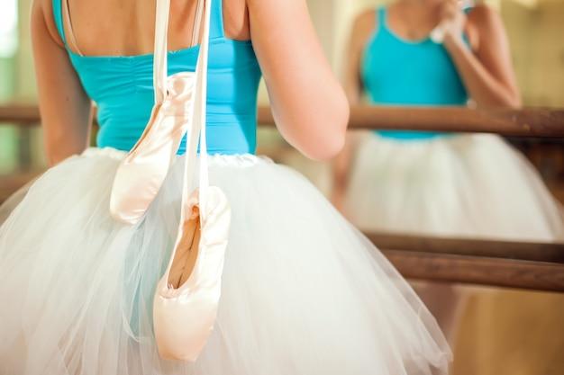 Donna al corso di danza classica tenendo le scarpe da punta davanti allo specchio. stile di vita e concetto di sport