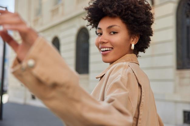 La donna balla e passeggia in città sorride esprime in modo ampio emozioni felici vestita con abbigliamento casual passeggiate in città passa per edifici antichi ha escursione nel tempo libero