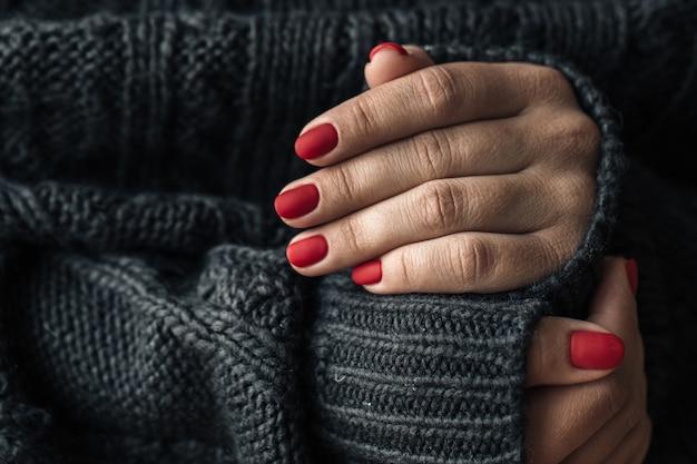 Una donna in un maglione lavorato a maglia scuro mostra un primo piano rosso del manicure.