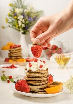 La donna decora le fragole con una pila di frittelle con panna montata