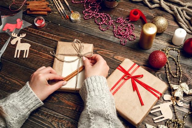 Donna che decora il regalo di natale