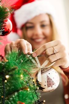 Donna che decora l'albero di natale con una palla bianca