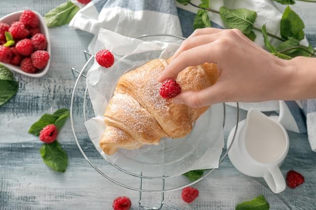 Donna che decora croissant con lampone, primo piano