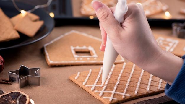 Donna che decora la casa di marzapane con glassa glassa crema topping
