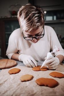 Donna che decora alcuni biscotti di panpepato fatti in casa in cucina