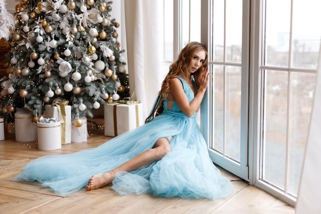 Donna in un delicato abito blu vicino alla finestra e albero di natale