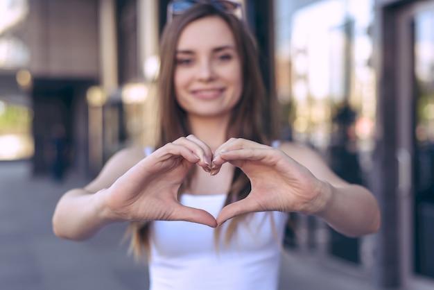 Donna che dimostra cuore con le dita