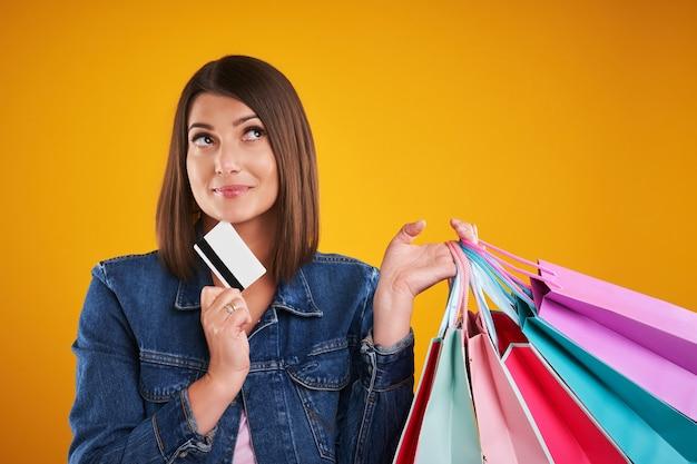 Donna in giacca di jeans con borse della spesa su sfondo giallo