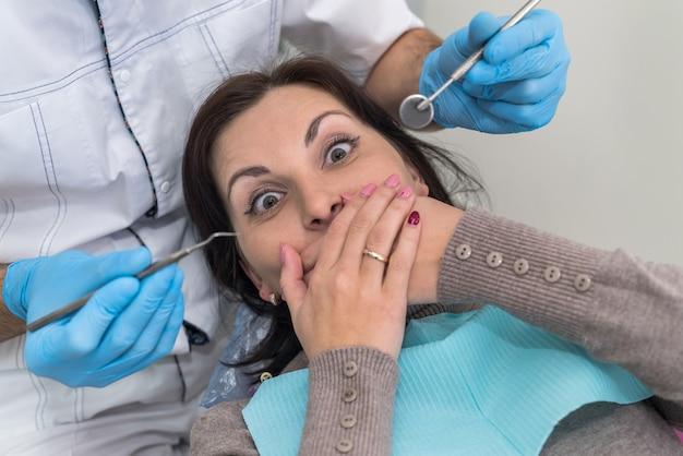 Donna in odontoiatria chiudendo la bocca con le mani