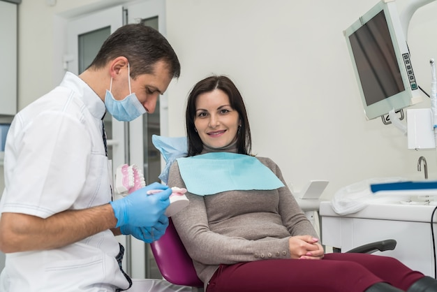 Donna in odontoiatria guardando il modello di protesi