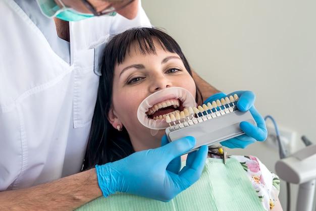 Donna in odontoiatria con campione di denti seduto in poltrona