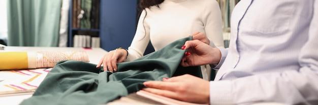 Progettista della donna che mostra il tessuto verde del cliente nel concetto di sviluppo di piccole imprese del salone delle tende