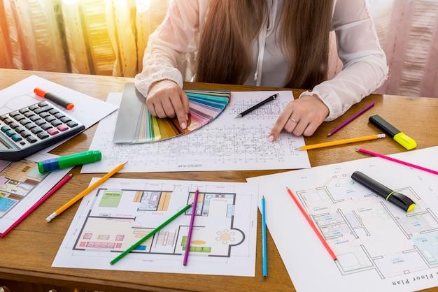 Designer donna con pianta della casa e campionatore di colori