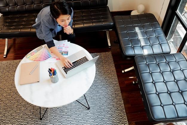 Progettista della donna che lavora online sul computer portatile