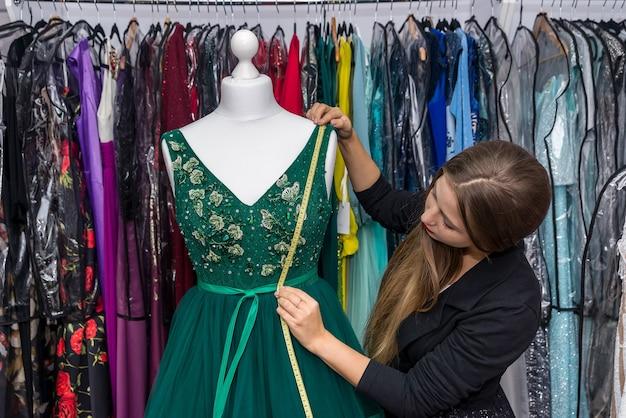 Stilista donna che lavora con il vestito e metro a nastro Foto Premium