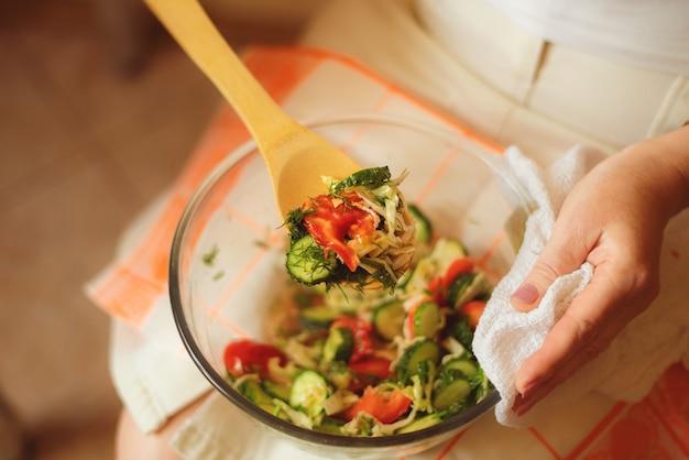 Donna a dieta con piatto di insalata cruda sulle ginocchia. concetto di disintossicazione sano