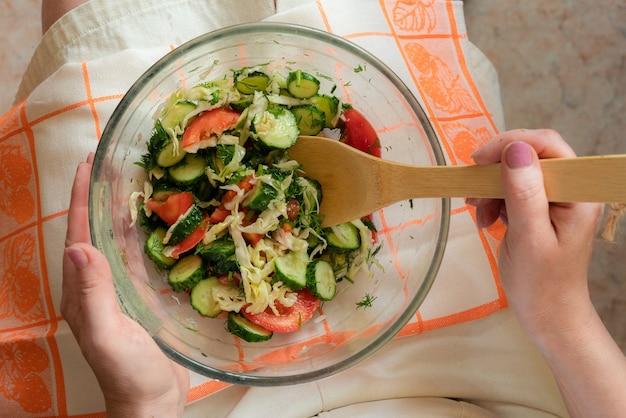 Donna a dieta con piatto di insalata cruda sulle ginocchia