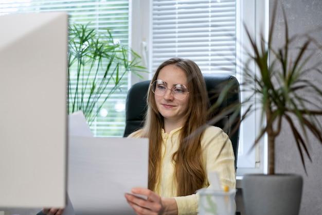 Direttore donna con gli occhiali si siede nel suo ufficio con il contratto in mano. il ragioniere tiene i documenti.
