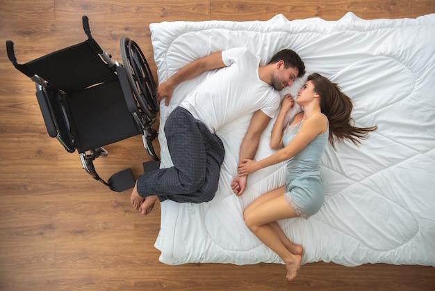 La donna e un uomo disabile sdraiati sul letto. vista dall'alto