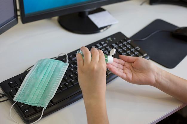 La donna disinfetta le mani con disinfettante sul posto di lavoro